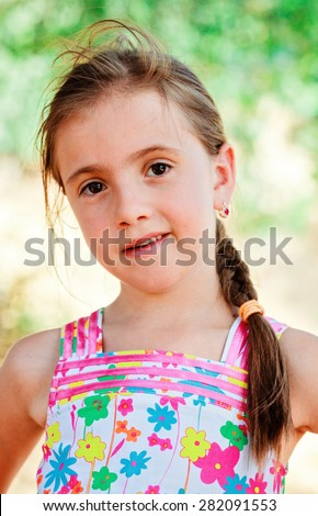 Summer portrait of little girl against green bokeh background