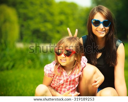Summer. Portrait of mother with daughter in sunglasses having on the meadow or in the park.