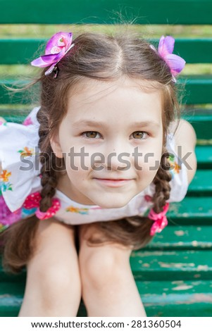 Summer portrait of smiling beautiful little girl with bows and braids in sundress. Selective focus on the face. - stock photo