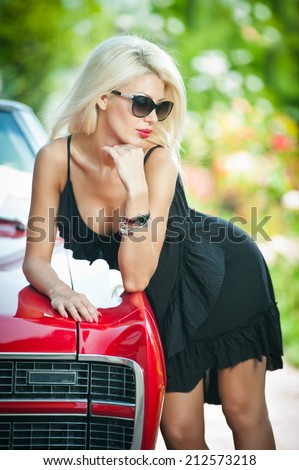 Summer portrait of stylish blonde vintage woman with black sunglasses bent over retro car. Fashionable attractive fair hair female leaning on red vintage vehicle. Sunny bright colors, outdoors shot. - stock photo