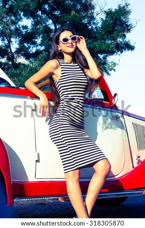 Summer portrait of stylish brunette vintage woman with long legs posing near red retro car. Fashionable attractive fair hair female near a red vintage vehicle. Sunny bright colors, outdoors shot.   - stock photo