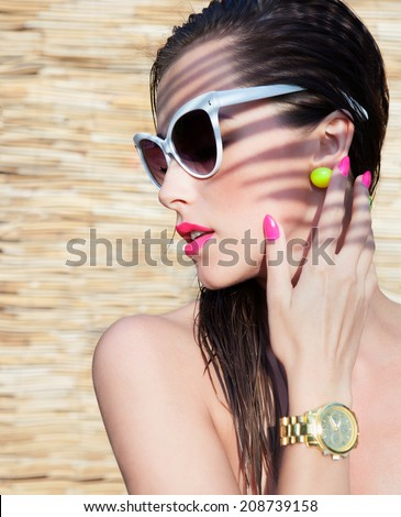 Summer portrait of young attractive elegant brunette woman wearing sunglasses and wrist watch under a palm tree