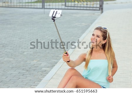 Summer portrait of young beautiful woman. Girl is photographed on the phone. Girl talking on the phone.