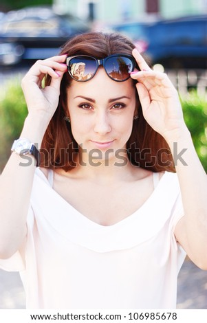 Summer portrait of young beautiful woman with brown eyes  and with sunglasses on a park background - stock photo