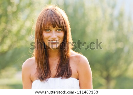 Summer portrait of young smiling woman against green natural background - stock photo