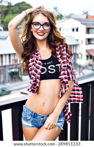 Summer portrait of young stylish hipster girl posing on balcony, wearing crop top, mini denim shorts, plaid shirt, clear glasses, sexy slim fit body, bright makeup, looking on camera.