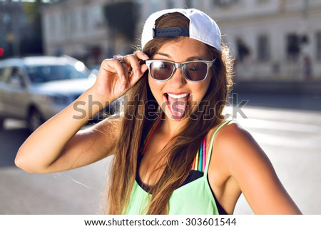 Summer portrait of young stylish hipster teen girl showing tongue, going crazy, swag neon street style look, sunny positive mood and emotions, travel alone at summertime. - stock photo