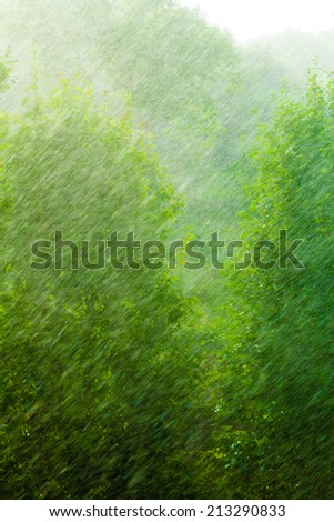 Summer rainy outside window, water drops droplets raindrops on glass windowpane as background texture. Downpour rain.