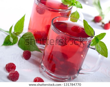 Summer raspberry cold drink (juice, cocktail, fruit tea) with mint on top.