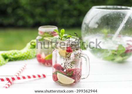 Summer refreshment drink. Water with raspberry, lime, ice, mint and thyme on rustic background. Pink Detox. - stock photo