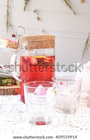 Summer Refreshment : Iced red berries tea, served with red rose petals in the ice cubes. Selective focus on the water drops - stock photo