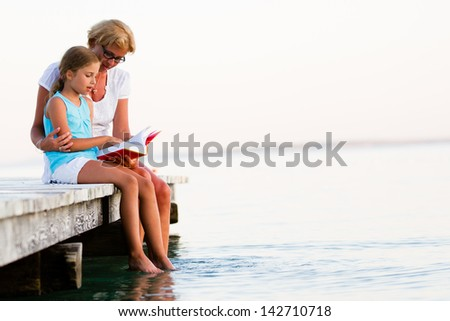Summer relax, girl with mother reading a book on the pier - stock photo