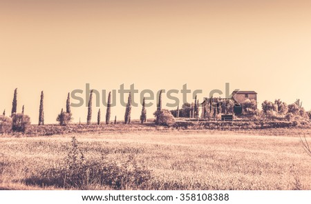 Summer retro landscape of tuscan farmhouse and cypress trees - stock photo