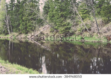 Summer river with reflections in Gauja National Park in Latvia - vintage effect
