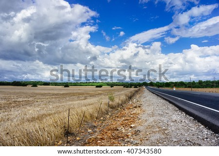 summer road with mountains and clouds on background. Road between hills and mountains. Rural road among fields. Asphalt road in countryside. Two-way road near mountains and fields. Road traffic. - stock photo