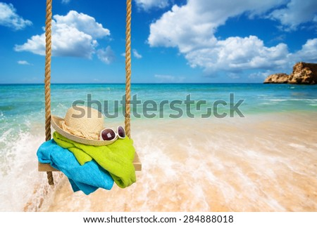 Summer rope swing with beach towels, sunhat and shades with beach blur background - stock photo