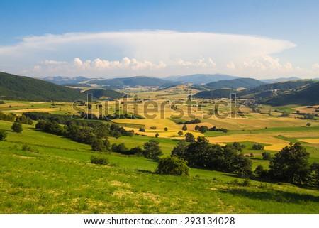 Summer rural landscape with big cumulonimbus in the sky. - stock photo