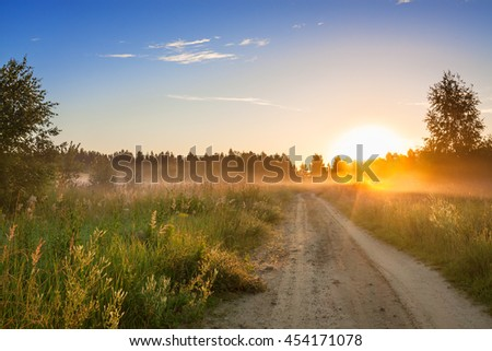 summer rural landscape with  blue sky, fog and the road.  sunrise - stock photo