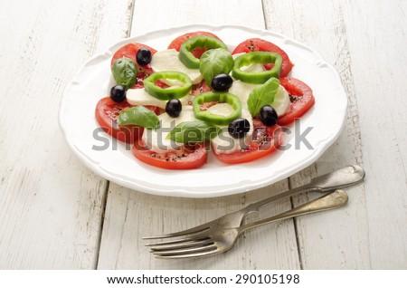 summer salad make from tomato, mozzarella, black olive, green chili and basil on a white plate - stock photo