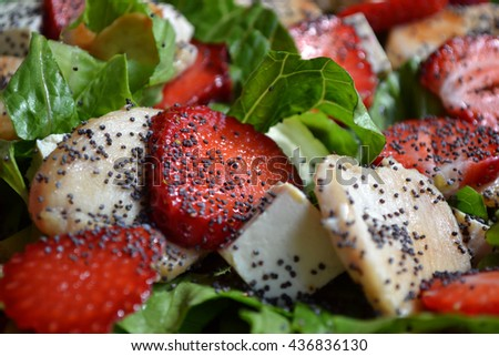 Summer salad with juicy  roasted turkey, red ripe strawberry slices, pieces of feta cheese, fresh green salad and poppy seeds. Seasonal dinner dish. Good idea for healthy eating. - stock photo