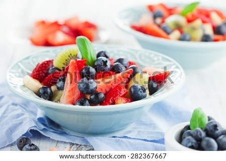 Summer salad with ripe fresh fruits and berries on white wooden background, selective focus