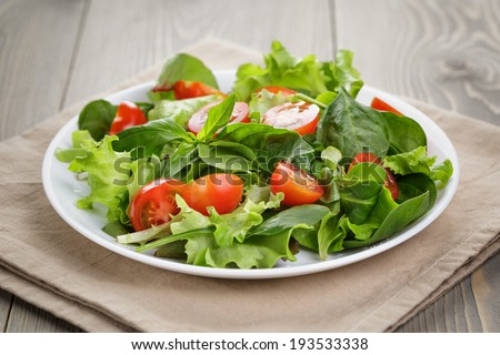 summer salad with tomatoes in white plate on wood table - stock photo