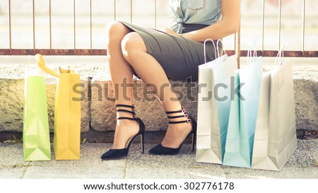 Summer sale. Close up of a sexy woman legs. Unrecognizable female person sitting next to lots of colorful shopping bags. She is wearing pencil skirt and trendy high heel shoes. - stock photo
