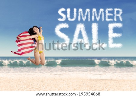 Summer sale clouds and woman jumping at beach - stock photo