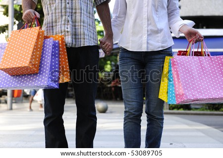 summer sale: couple with shopping bags crossing the street - stock photo