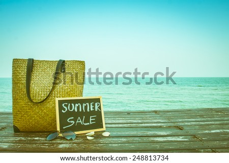 summer sale decorate with bamboo bag and chalkboard on wooden floor on the blue sea. - stock photo