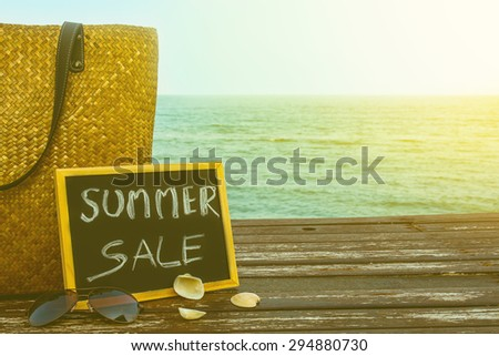 summer sale decorate with bamboo bag and chalkboard on wooden floor over blue sea background,vintage color filter. - stock photo
