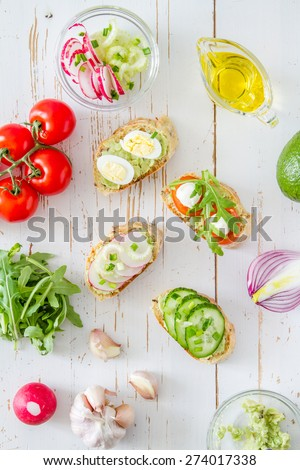 Summer sandwiches ingredients - avocado, cucumber, radish, tomato, mozzarella and eggs, white wood background, top view - stock photo