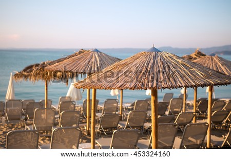 Summer sandy beach with blue ocean with sunbed on background