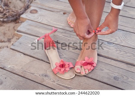 Summer scene: a girl putting on coral sandals at the beach sundeck - stock photo