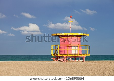 Summer scene in Miami Beach Florida, with a colorful lifeguard house in a typical Art Deco architecture, with ocean and sky in the background.