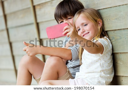 Summer scene of Happy young brothers taking selfies with her smartphone in the park - stock photo