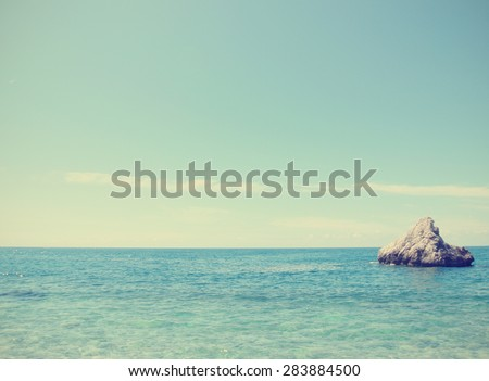 Summer seascape on a clear sunny day - turquoise water and clear blue sky. Image filtered in faded, washed out, retro style; nostalgic summer vintage concept. - stock photo