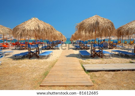 Summer season, scene from the beach with people and sun beds.