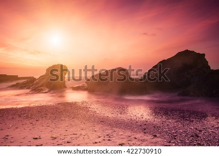 Summer seasonal natural vacation background. Romantic morning at sea. Big boulders sticking out from smooth wavy sea. Pink horizon with first hot sun rays. Long exposure.  - stock photo