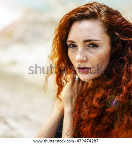 Summer serious portrait, beautiful freckled young adult girl with red hair look down. Cute curly redhead woman dreaming or thinking against outdoor background
