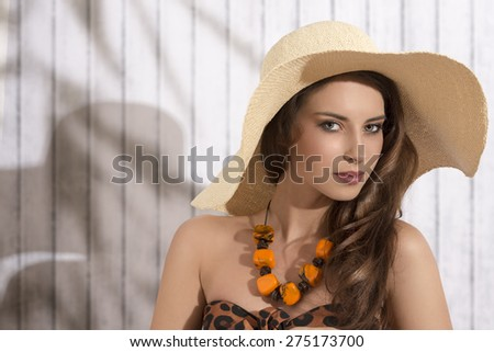 summer shoot of sexy brunette lady posing with sensual expression and long natural hair. Wearing big straw hat and stylish bikini and necklace - stock photo