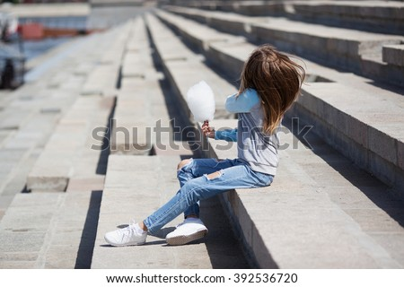 Summer shot. The girl sits on the waterfront with cotton candy in hand. Casual summer style. The model wears light blue and gray colors of the clothes. Face of models closed by her hair