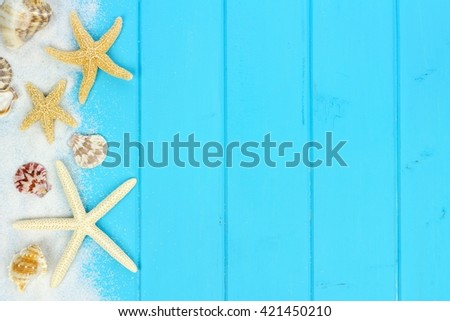 Summer side border of sand, sea shells and star fish on blue wooden background - stock photo