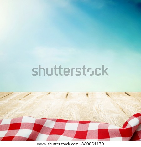 Summer sky with wooden picnic table in red tablecloth - stock photo
