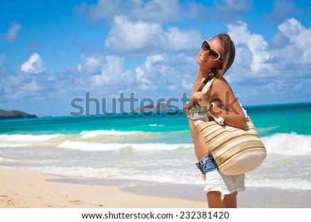 Summer smile. Beautiful young woman with well toned body walking along the seashore, Honolulu, Hawaii - stock photo
