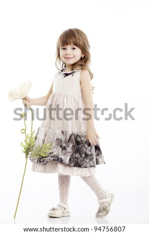 Summer smiling portrait of a little girl playing with a flower - stock photo