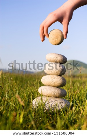 Summer. Someone's hand constructs equilibrium on a grass. - stock photo