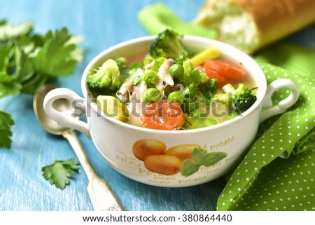 Summer soup with chicken and vegetables on a blue table. - stock photo
