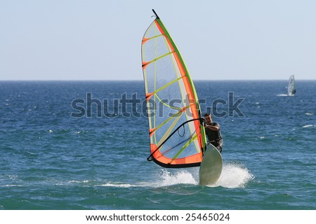 summer sports: windsurfer with bright colored sail on Algarve blue water, south of Portugal - stock photo