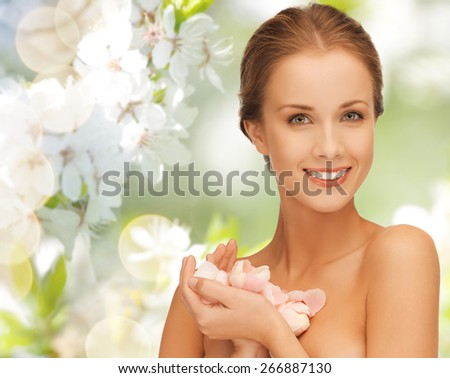 summer, spring, beauty, people and health concept - beautiful young woman holding flower petals over green blooming garden background - stock photo